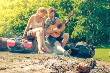 camp fire: Adventure, tourism, enjoying summer time together - young couple tourists having fun playing guitar in camping outdoor Stock Photo