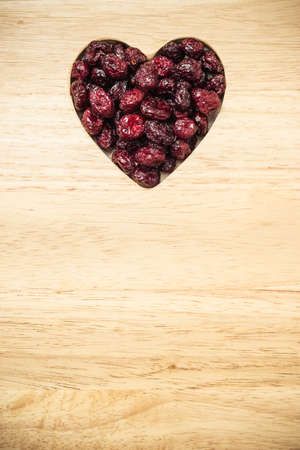 fiber food: Healthy high fiber food, organic nutrition. Dried cranberries cranberry fruit in shape of heart on wooden surface background Stock Photo