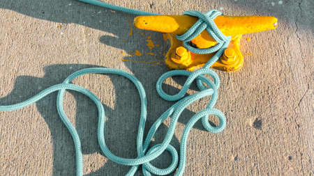 mooring bollard: Yellow mooring bollard with blue rope in marina closeup Stock Photo