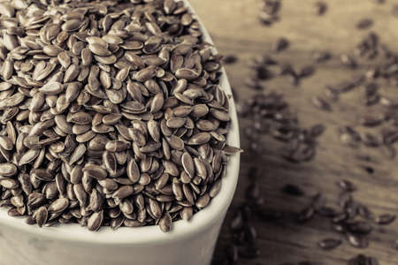 brown flax: Healthy food diet. Brown flax seeds linseed in white bowl on wooden table Stock Photo