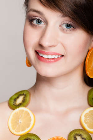 recommending: Diet. Girl with necklace and earrings of fresh citrus fruits on gray. Woman recommending healthy food and nutrition. Stock Photo