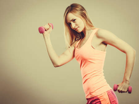 weights: Bodybuilding. Strong fit woman exercising with dumbbells. Muscular blonde girl lifting weights studio shot