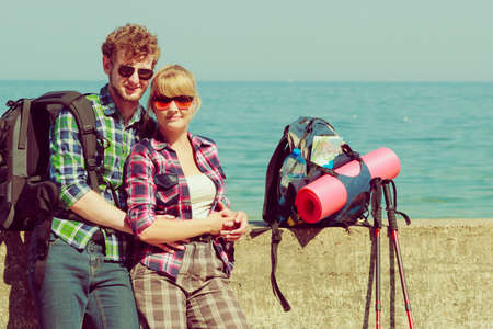 tramping: Adventure, summer, tourism active lifestyle. Young couple backpacker tramping by seaside Stock Photo