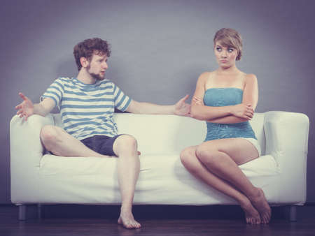 relationship problems: Bad relationship concept. Man and woman in disagreement. Young couple sitting on couch at home having quarrel, offended wife and unhappy husband Stock Photo