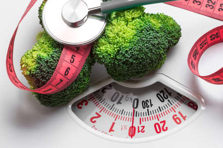 weight control: Diet healthy eating weight control concept. Closeup green broccoli with measuring tape and stethoscope on white scales