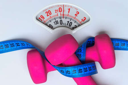 scales thin: healthy lifestyle fitness weight control concept. Closeup pink dumbbells with blue measuring tape on white scales Stock Photo