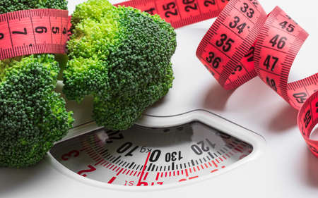 Dieting healthy eating slim down weight control concept. Closeup green broccoli with measuring tape on white scales Standard-Bild