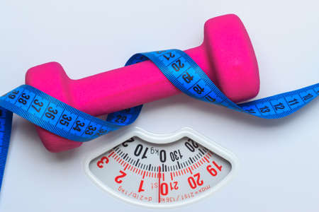 WEIGHT: healthy lifestyle fitness weight control concept. Closeup pink dumbbell with blue measuring tape on white scales Stock Photo