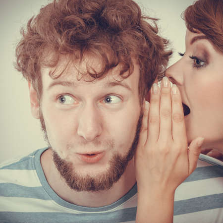 astonishment: Closeup woman telling an astonished surprised man some secrets, couple talking Stock Photo