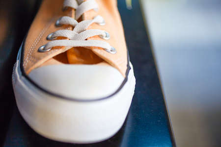 plimsoll: Sport fashion. Closeup orange fashionable sneakers on shop shelf Stock Photo