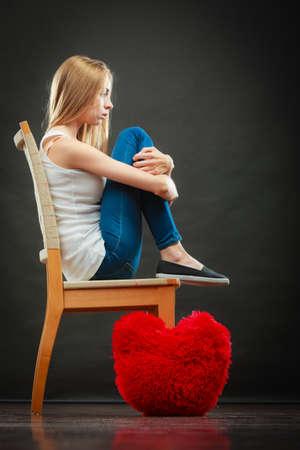 broken chair: Broken heart love concept. Sad unhappy woman sitting on chair red heart pillow on floor dark background Stock Photo