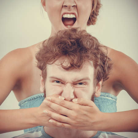 couple having argument - conflict, bad relationships. Angry fury woman screaming while covering with hand mouth of her fury man