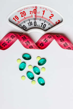 diet food: Healthy eating, medicine, health care, food supplements and weight loss concept. Pills with measuring tape on white scales