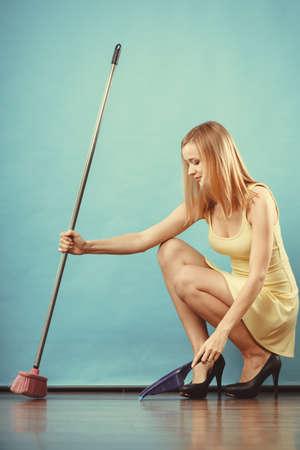 brooming: Cleanup housework concept. Elegant sensual woman sweeping wooden floor with broom.