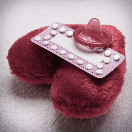 safe sex: Medicine contraception love and birth control. Oral contraceptive pills condom on red heart shaped little pillow Stock Photo