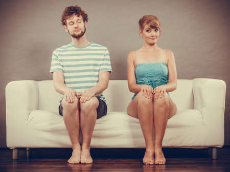 Relazione di concetti. Shy donna e uomo seduto vicino a vicenda sul divano.