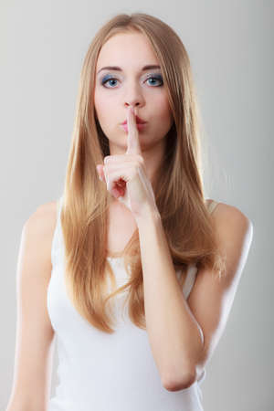 secrecy: Closeup woman asking for silence or secrecy with finger on lips hush hand gesture, on gray background