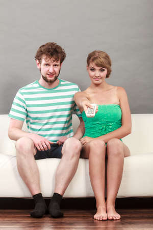 changing channel: watching television - couple sitting on couch with remote control changing channel Stock Photo