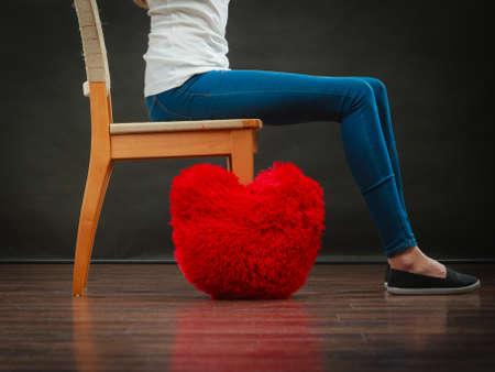 broken chair: Broken heart love concept. woman sitting on chair red heart pillow on floor dark background