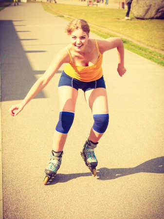 blading: Holidays, active lifestyle freedom concept. Young fit woman on roller skates riding outdoors on street, girl rollerblading on sunny day
