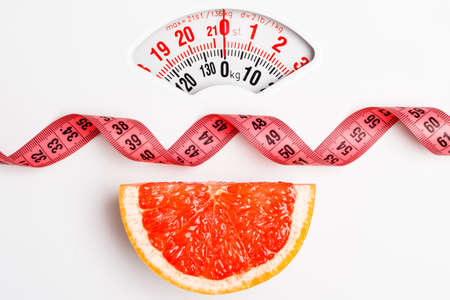 Dieting healthy eating slim down concept. Closeup grapefruit slice with measuring tape on white weight scale Foto de archivo
