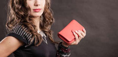 Fashion elegant evening outfit. Close up elegant woman holding red leather handbag clutch bag on dark background Foto de archivo