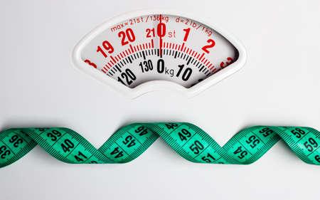 Dieta perdita di peso sottile concetto giù. Primo piano di misurazione nastro su bianco scala del peso di testo copia spazio