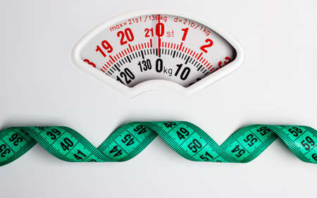 Dieting weightloss slim down concept. Closeup measuring tape on white weight scale copy space text area Stockfoto