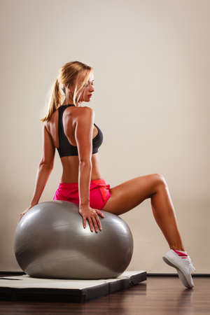 fit ball: Sport, training, gym and lifestyle concept. Young attractive slim woman in sportwear doing fitness exercises with fit ball at home