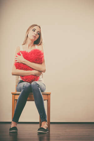heartbreak issues: Broken heart love concept. Sad unhappy woman hugging red heart pillow