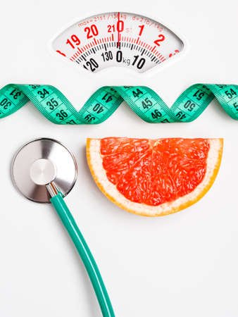 weight control: Diet healthy eating weight control concept. Grapefruit with measuring tape and stethoscope on white scales