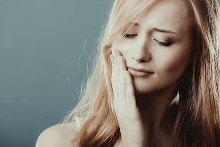 Cuidado dental y dolor de muelas. Primer rostro de mujer joven preocupado niña sufre de dolor de dientes fondo gris pared azul