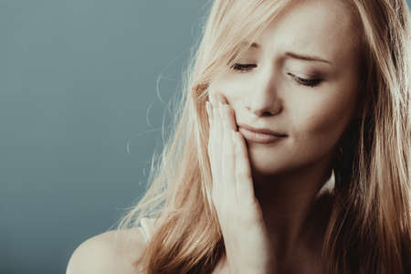 Dental care and toothache. Closeup young woman face worried girl suffering from tooth pain gray blue wall background