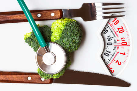 weight control: Diet healthy eating weight control and health care concept. Closeup green broccoli with stethoscope knife fork on white scales Stock Photo