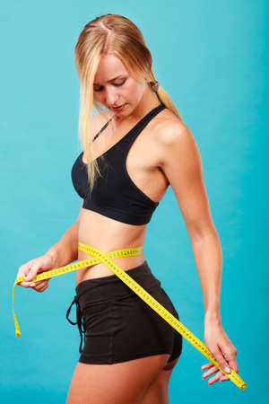 slim tummy: Weight loss, slim body, healthy lifestyle concept. Fit fitness girl measuring her waistline with measure tape on blue