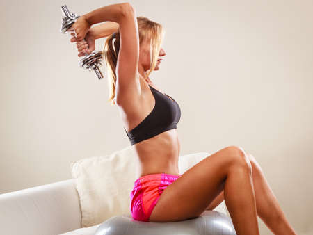active lifestyle: Healthy active lifestyle. Fitness woman with gym ball and dumbbell doing exercise Stock Photo