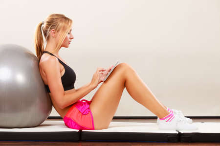 home trainer: Fitness woman blonde fit girl sitting on floor and looking into tablet pc