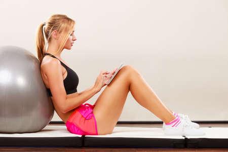 Mulher da aptidão ajuste garota loira sentada no chão e olhando para tablet pc Imagens