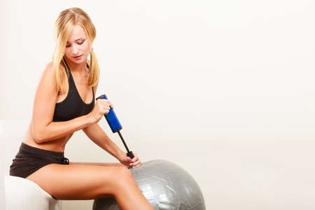 inflating: Sport, training, gym and lifestyle concept. Young attractive slim woman in sportwear with air pump inflating fit ball, fitness exercise