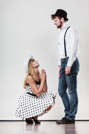 Girlriend trying to convince boyfriend. Woman on knees asking begging for forgivness. Conflicted young couple. Relationship problem. Stock Photo