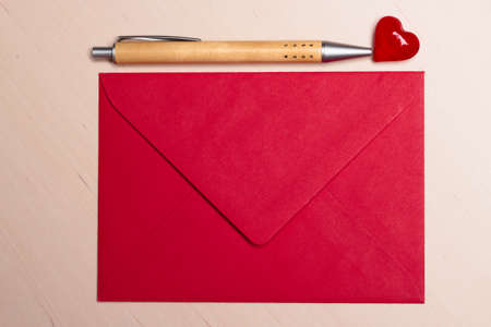 notecard: Red blank envelope little heart and pen on wooden surface. Valentine day card, love or wedding greeting concept.