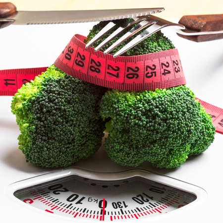 diet food: Diet healthy eating weight control concept. Closeup green broccoli measuring tape and fork knife on white scales