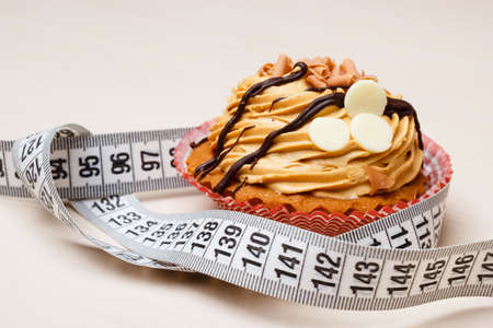 fattening: Appetite and gluttony concept. Fattening problem. Cake cupcake with measuring tape on table