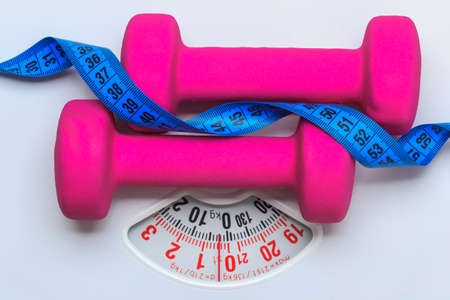weight control: healthy lifestyle fitness weight control concept. Closeup pink dumbbells with blue measuring tape on white scales Stock Photo