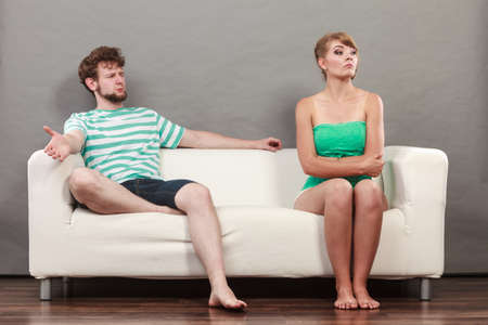 sullenly: Bad relationship concept. Man and woman in disagreement. Young couple sitting on couch at home having quarrel, offended wife and unhappy husband Stock Photo