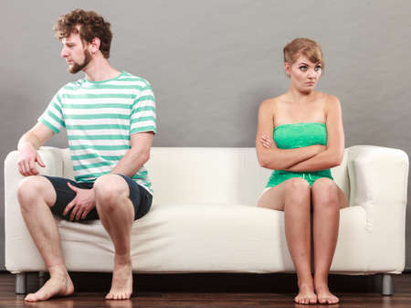sullenly: Bad relationship concept. Man and woman in disagreement. Young couple after quarrel sitting offended on couch