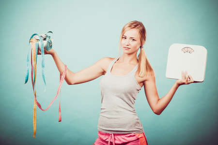 fat: Diet, healthy eating and slim body concept. Fit fitness girl holding bowl with many colorful measuring tapes as dieting symbol and weight scales studio shot on blue
