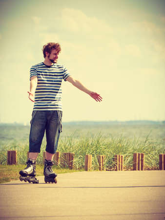 rollerskates: Holidays, active lifestyle freedom concept. Young fit man on roller skates riding outdoors on sea coast, guy rollerblading on sunny day