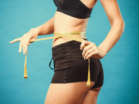 weight control: Weight loss, slim body, healthy lifestyle concept. Fit fitness girl measuring her waistline with measure tape on blue
