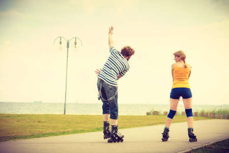 rollerskates: Holidays, active people and friendship concept. Young fit couple on roller skates riding outdoors on sea shore, woman and man rollerblading together on the promenade Stock Photo
